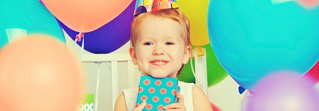 Kind glücklich mit einem Geschenk und Luftballons