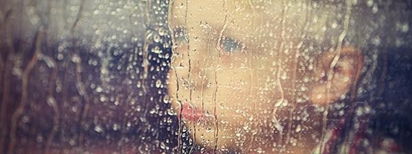 Junge schaut an einem Regentag aus dem Fenster