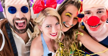 4 fröhliche Menschen in Kostümen
