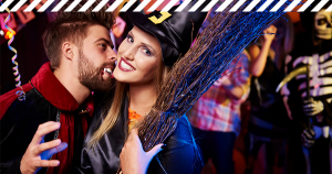 Mann im Vampir Kostüm beißt Frau im Hexenkostüm