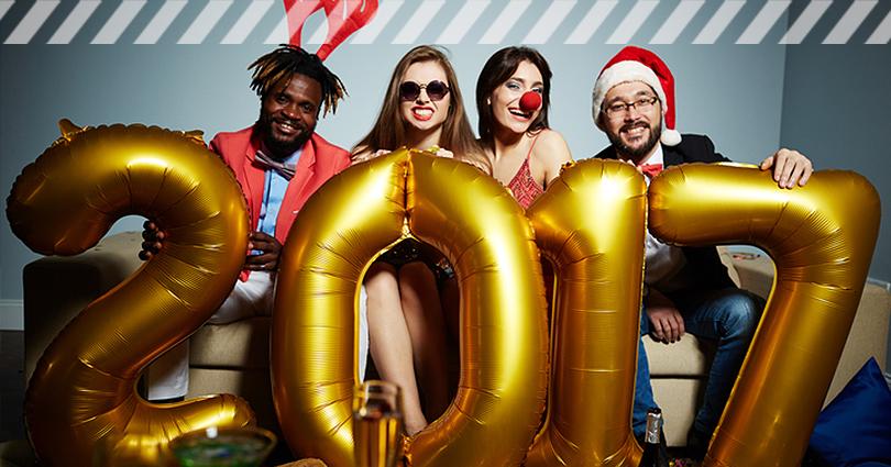 Vier Leute in Kostümen, die auf dem Sofa sitzen und eine goldene 2017 halten