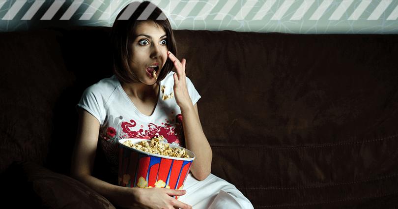 Junge Frau sitzt mit Popcorn vorm TV und schaut Horrorfilme