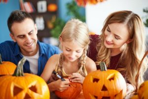 Familie beim Halloween Kürbis schnitzen - Mädchen malt Gesicht auf Kürbis