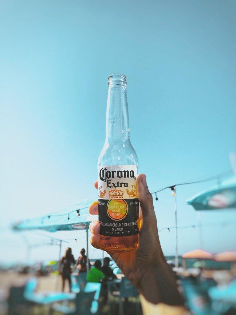 Hand hält Corona Extra Bier Flasche