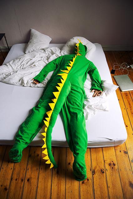 Mensch in Dinosaurier Kigurumi auf Bett