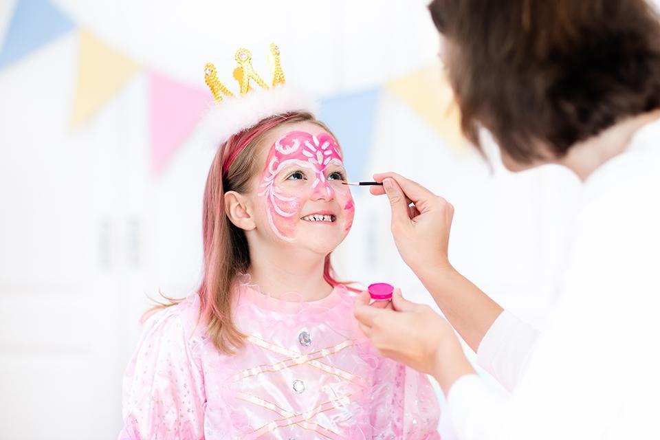 Frau schminkt kleines Mädchen als Prinzessin