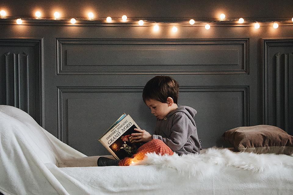 Junge auf Bett und liest Buch