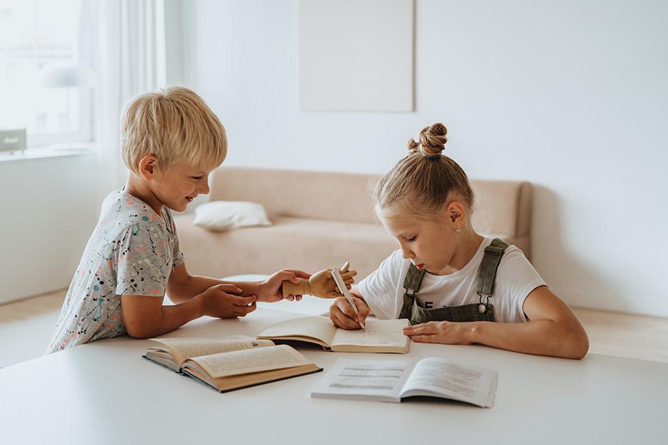 Junge und Mädchen schreiben in Buch