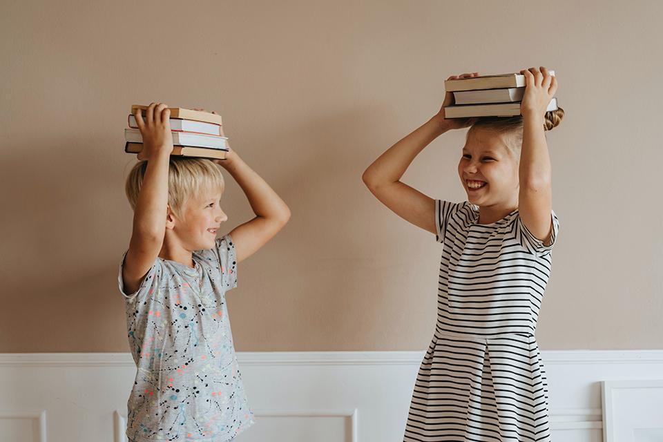 Kinder mit Bücherstapel auf dem Kopf