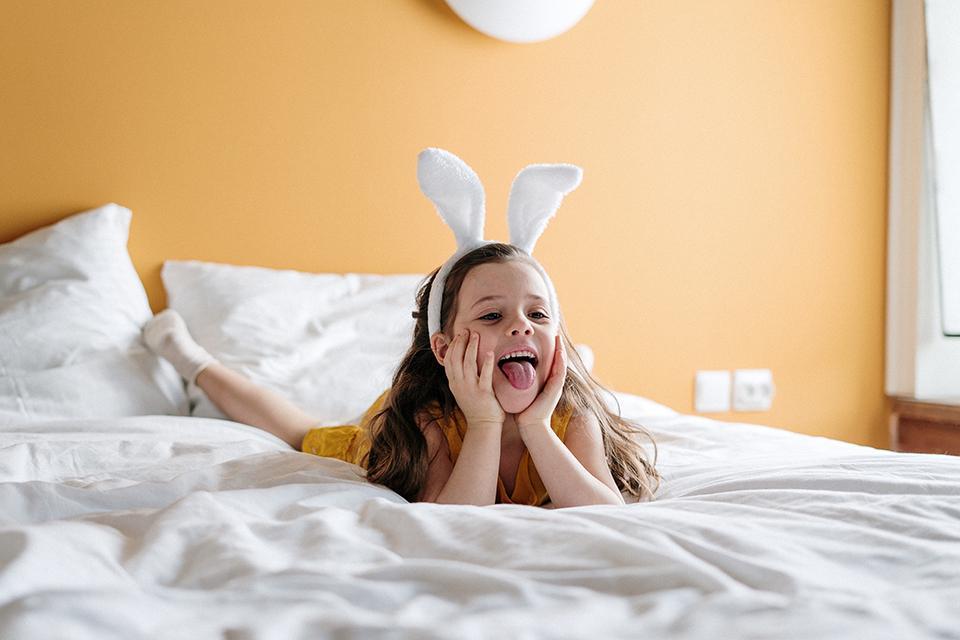 Mädchen liegt auf Bett mit Hasenhaarreif