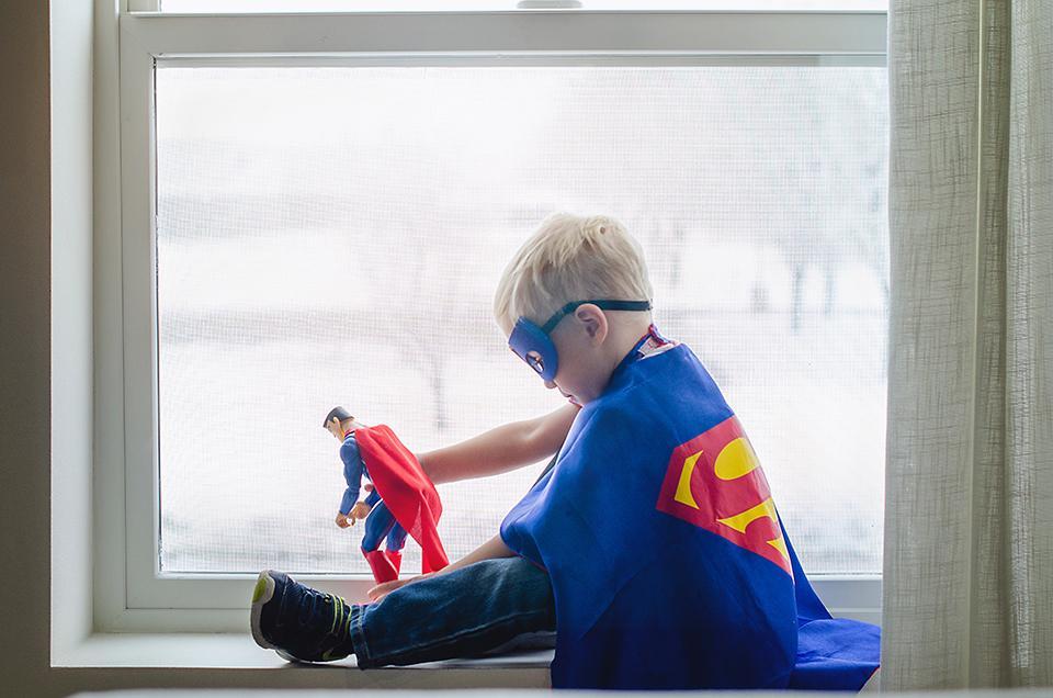 Junge mit Superman Kostüm spielt Superheldenfigur