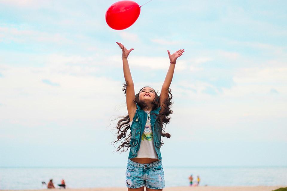 Kind am Strand mit rotem Luftballon