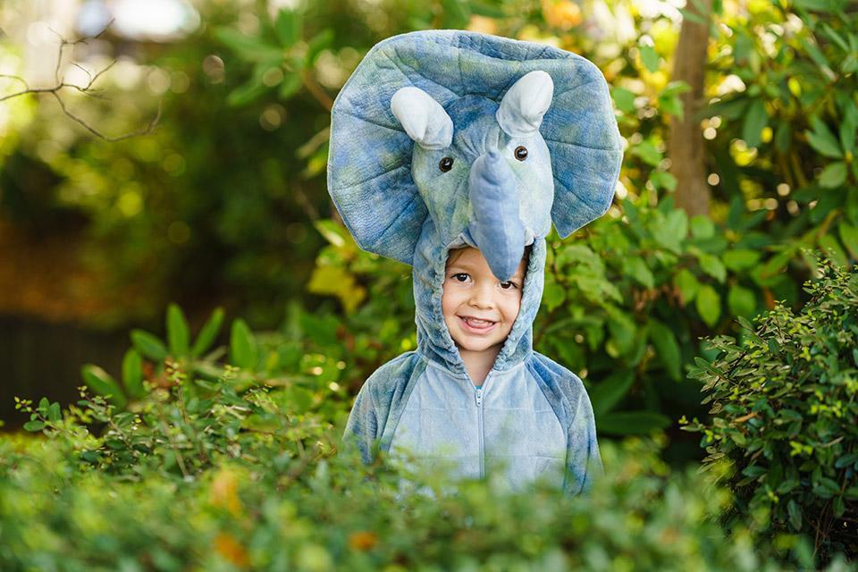 Kind mit Dinosaurier Kostüm im Garten