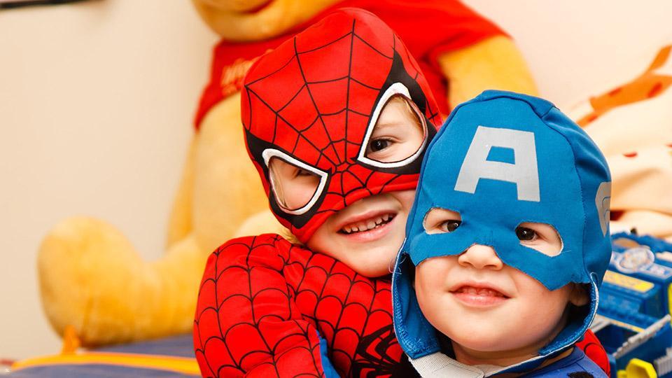 Spielende Kinder mit Superhelden Kostümen